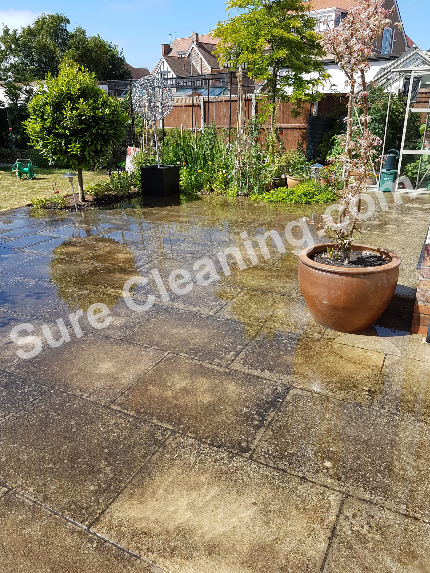 Patio with black spot before being pressure cleaned